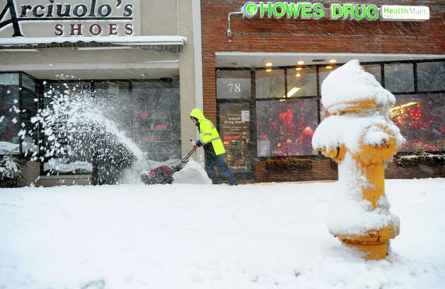 Bailey Pelep, with L&W Contracters, uses a snow blower to remove snow in front a row of businesses along Braod Street as a major snow storm hits the region in Milford Conn. on Friday February 8, 2013. Photo: Christian Abraham / Connecticut Post