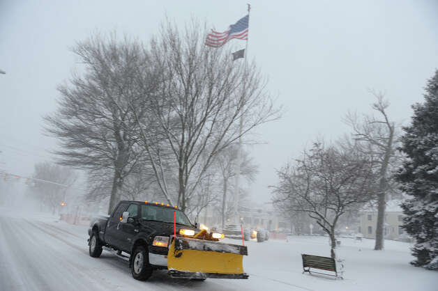 A truck with a plow zips by on Broad Street as a major snow storm hits the region in Milford Conn. on Friday February 8, 2013. Photo: Christian Abraham / Connecticut Post