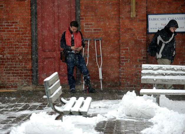 A couple of commuters seek shelter from the storm at the train station in downtown Fairfield, Conn. on Friday, Feb. 8, 2013. According to the National Weather Service, southern Fairfield County could get 10 to 14 inches; northern Fairfield County from 12 to 16 inches. Photo: Cathy Zuraw / Connecticut Post
