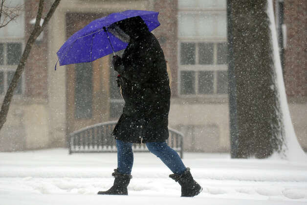 A woman walks in the snow across McLevy Green, in downtown Bridgeport, Conn., Feb. 8th, 2013. Photo: Ned Gerard / Connecticut Post