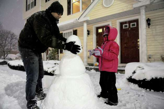 Drishti Duggal, 7, and her father, Sunil, make a snowman in Stamford, Conn., during the blizzard Friday, February 8, 2013. Photo: Lindsay Perry / Stamford Advocate