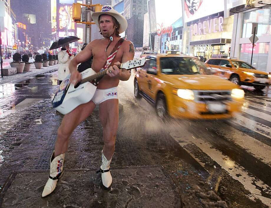 "Robert Burck, aka the ""Naked Cowboy,"" performs in Times Square as it snows Friday, Feb. 8, 2013, in New York. Snow began falling across the Northeast on Friday, ushering in what was predicted to be a huge, possibly historic blizzard and sending residents scurrying to stock up on food and gas up their cars. The storm could dump 1 to 3 feet of snow from New York City to Boston and beyond.  Photo: Frank Franklin II, Associated Press"