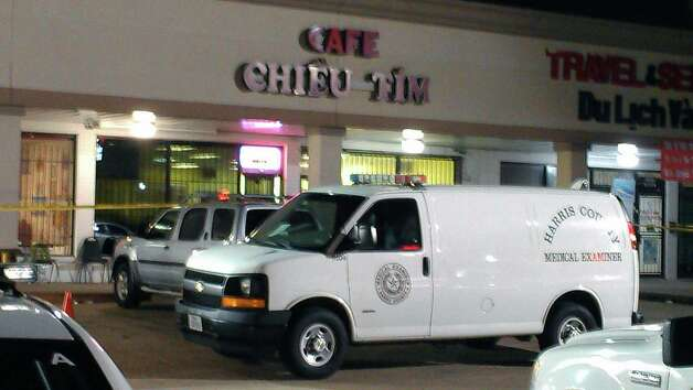 A medical examiner van sits outside the scene of the slaying. Photo: Mike Glenn/Chronicle