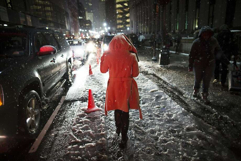 Snow falls on a pedestrian as she leaves the Rag & Bone Fall 2013 fashion collection show during Fashion Week, Friday, Feb. 8, 2013, in New York. Snow began falling across the Northeast on Friday, ushering in what was predicted to be a huge, possibly historic blizzard and sending residents scurrying to stock up on food and gas up their cars. Photo: John Minchillo, Associated Press