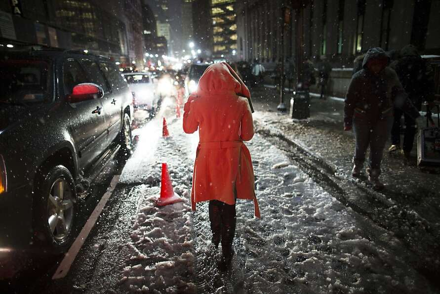 Snow falls on a pedestrian as she leaves the Rag & Bone Fall 2013 fashion collection show during Fas