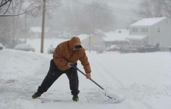 Rick Lucibella shovels his driveway in Shelton, Conn. Friday, Feb. 8, 2013 as a steady snowfall blankets the state.  Lucibella said his road had yet to be plowed and one neighbor slid into a fence on his return home. Photo: Autumn Driscoll