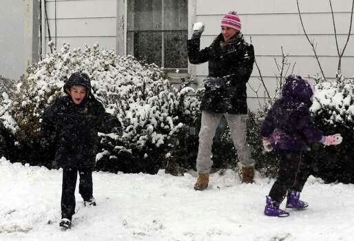 Jennifer Bacsik aims for 6-year-old Trevor Whittaker during a snowball fight Friday, Feb. 8, 2013 in Derby, Conn. Photo: Autumn Driscoll
