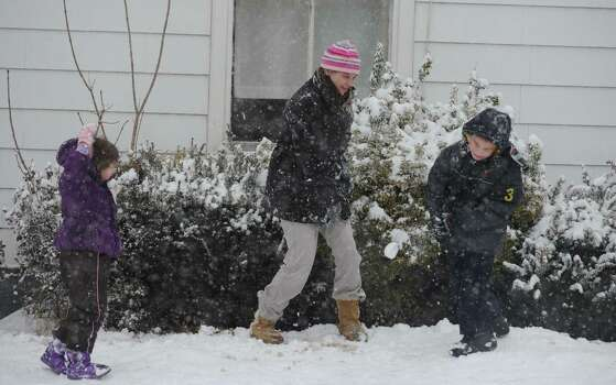 Jennifer Bacsik and her daughter Joelle Branscomber, 4, and Trevor Whittaker, 6, take part in a snowball fight Friday, Feb. 8, 2013 in Derby, Conn. Photo: Autumn Driscoll