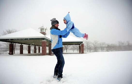 Jamie Bratt and her 15-month-old daughter Mina spin around in the snow at Veteran's Memorial Park in Shelton, Conn. Friday, Feb. 8, 2013. Photo: Autumn Driscoll
