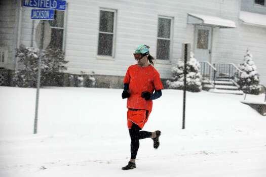 A man runs down Westfield Avenue in Ansonia, Conn. as snow falls Friday, Feb. 8, 2013. Photo: Autumn Driscoll