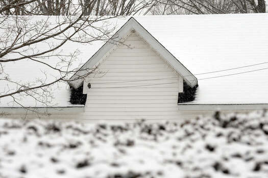 Snow covers a roof on a building off of Route 67 at the start of a major snow storm hitting our area today in Seymour, Conn. on Friday February 8, 2013. Photo: Christian Abraham / Connecticut Post