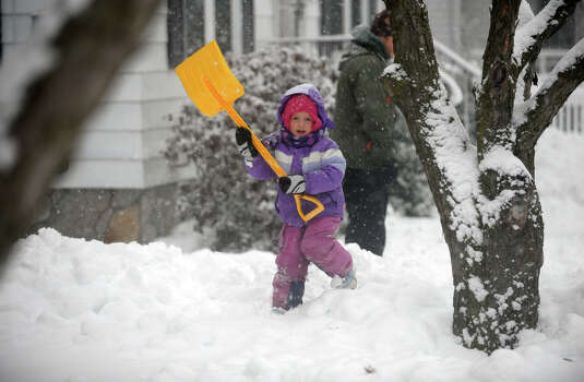 Hannah Newman, 4, plays with her shovel in the snow as her other family members shovel the sidewalks on Darina Place in Milford Conn. on Friday February 8, 2013. Photo: Christian Abraham / Connecticut Post