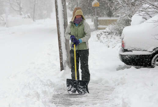 Michelle Newman shovels the snow on her sidewalk at her home on Darina Place in Milford Conn. on Friday February 8, 2013. Photo: Christian Abraham / Connecticut Post