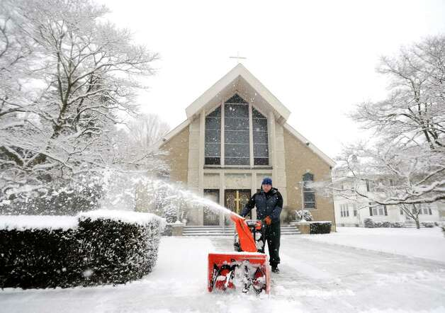 Parishioner Peter Schumann clears the walkways at St. Anthony's Church on South Pine Creek Rd. in Fairfiled, Conn. on Friday, Feb. 8, 2013. Several inches of slick, heavy snow have already fallen across southwestern Connecticut and will steadily increase this afternoon and evening. Photo: Cathy Zuraw / Connecticut Post