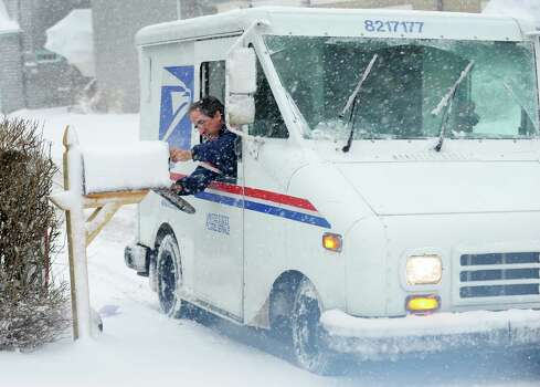 "John David Bravo aka ""Johnnny Bravo"" delivers mail as heavy snow continued to fall on Fairfield Beach Rd.in Fairfield, Conn. on Friday, Feb. 8, 2013. According to the National Weather Service, southern Fairfield County could get 10 to 14 inches. Photo: Cathy Zuraw / Connecticut Post"