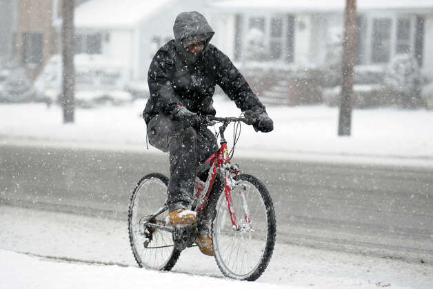 Terence LaRose, of Stratford, rides his bicycle in the snow along Main Street, in Stratford, Conn., Feb. 8th, 2013. Photo: Ned Gerard / Connecticut Post