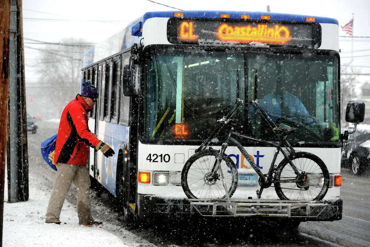 A rider boards a Greater Bridgeport Transit bus as the snow begins to fall along Main Street, in Bridgeport, Conn., in Stratford, Conn., Feb. 8th, 2013.
