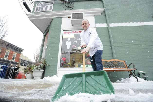 Executive Deli manager Paul McQuillan clears snow from in front of his store in the downtown section of Byram during the snowstorm that hit Greenwich, Conn., Friday, Feb. 8, 2013. Photo: Bob Luckey / Greenwich Time
