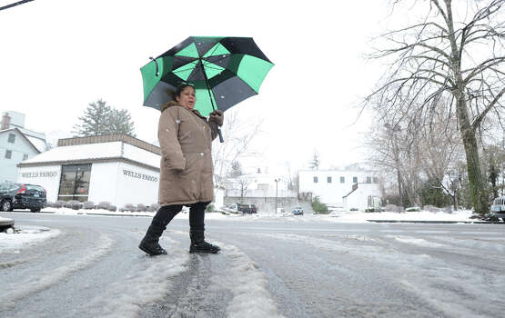 Anna Garcia uses an umbrella to shield herself while walking on South Water Street during the snowstorm that hit the Byram section of Greenwich, Conn., Friday, Feb. 8, 2013. Photo: Bob Luckey / Greenwich Time