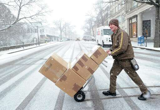 UPS deliveryman Bobby Whritenour crosses a snowy and deserted Greenwich Avenue while making his rounds during the snowstorm that hit Greenwich, Conn., Friday, Feb. 8, 2013. Photo: Bob Luckey / Greenwich Time