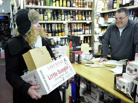 At left, Shannon Bassalik of Cos Cob holds a box of alcohol she purchased from Randy Caravella, right, owner of Post Wines & Spirits in Cos Cob, for an upcoming ski trip, during the storm that hit Greenwich, Conn., Friday, Feb. 8, 2013. Photo: Bob Luckey / Greenwich Time