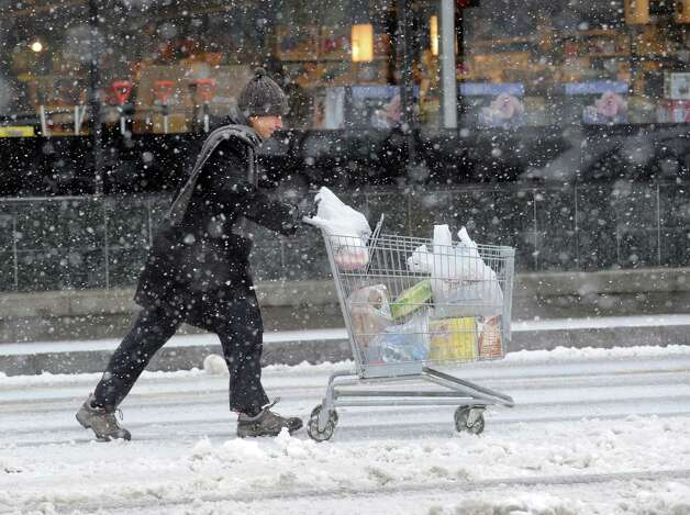 A shopper with a cart filled with groceries heads to his car in the Riverside Commons during the snowstorm that hit Greenwich, Conn., Friday, Feb. 8, 2013. Photo: Bob Luckey / Greenwich Time