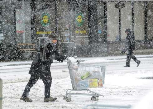 A shopper with a cart filled with groceries heads to his car in the Riverside Commons Shopping Plaza during the snowstorm that hit Greenwich, Conn., Friday, Feb. 8, 2013. Photo: Bob Luckey / Greenwich Time