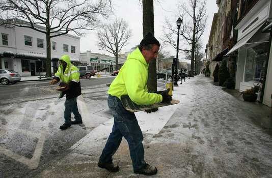 Greenwich Department of Public Works employees Ricky Enoch, left, and Tom Marturano spread salt on Greenwich Ave. Friday, Feb. 8, 2013. Photo: David Ames / Greenwich Time Freelance
