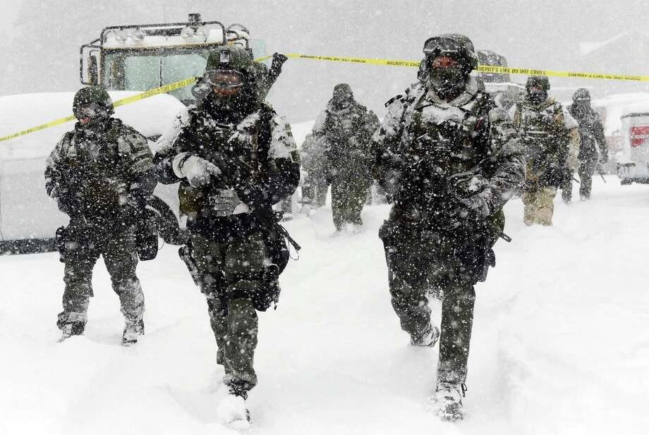 A San Bernardino County Sheriff SWAT team returns to the command post at Bear Mountain near Big Bear Lake, Calif. after searching for Christopher Jordan Dorner on Friday, Feb. 8, 2013. Search conditions have been hampered by a heavy winter storm in the area. Dorner, a former Los Angeles police officer, is accused of carrying out a killing spreebecause he felt he was unfairly fired from his job. (AP Photo/Pool, The Inland Valley Daily Bulletin, Will Lester) Photo: Will Lester, POOL / The Inland Valley Daily Bulletin