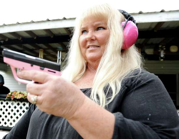 Brenda Wells Deshotel shows us her Taurus 738 Pink TCP .380 handgun on Friday, February 8, 2013 , at her home in Orange.  Deshotel received it for Christmas this past December. She also prides herself on her pink Winchester earmuffs. Photo taken: Randy Edwards/The Enterprise