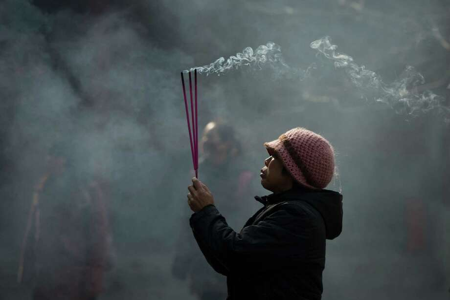 A worshipper burns incense while offering prayers at the Yonghegong lama temple in Beijing on February 8, 2013. China is preparing to welcome the lunar new year, or spring festival, which falls on Febraury 10. Photo: ED JONES, AFP/Getty Images / AFP
