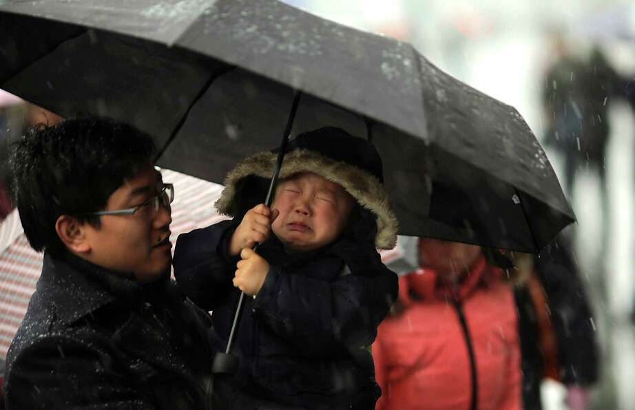 A child held by his father cries as he holds an umbrella in the snow at the Shanghai Railway Station