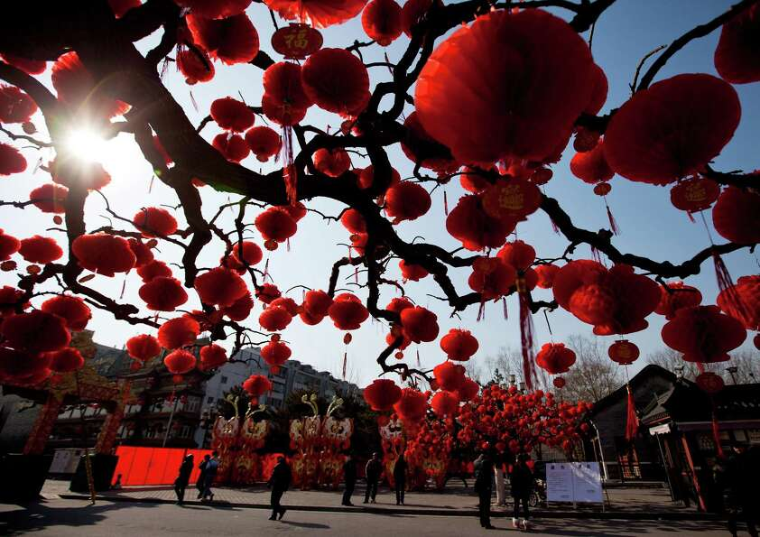 Visitors stroll near the trees decorated with red lanterns ahead of Chinese New Year celebrations at