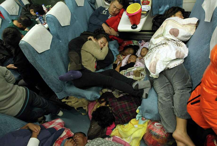 People sleep on their seats on the train from Guangzhou to Changchun to go back home for the Lunar New Year, or Spring Festival.  Passengers will log 220 million train rides during the 40-day travel season as they criss-cross the country to celebrate with their families, but just as making the trip home can be laborious -- often lasting one or two days -- so can simply acquiring a seat on the train, and every year complaints arise about the inefficiency or unfairness of the system, although an initiative allowing travelers to purchase tickets online aims to curb long queuing times. Photo: STR, AFP/Getty Images / AFP