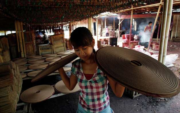 An Indonesian worker carries circle incense sticks prepared for Chinese New Year celebrations, in Tangerang on the outskirts of Jakarta, Indonesia, Monday, Feb. 4, 2013. The Chinese Lunar New Year falls on Feb. 10. Photo: Achmad Ibrahim, Associated Press / AP