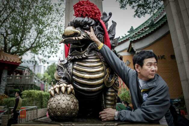 A man touches a statue for good fortune at the entrance of a Taoist temple in Hong Kong in Hong Kong on February 7, 2013.  A stock market slide, escalated conflict between Japan and China and more Gangnam-styled success for South Korean singer Psy will shape the incoming Year of the Snake, say Asian soothsayers. February 10 marks the first day of the Lunar New Year across the region. Photo: PHILIPPE LOPEZ, AFP/Getty Images / AFP