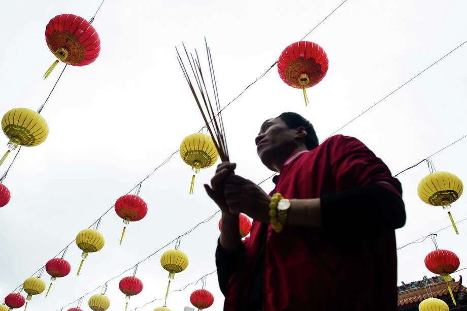 A man holds incense sticks under a display of lanterns at a Taoist temple in Hong Kong in Hong Kong on February 7, 2013.  A stock market slide, escalated conflict between Japan and China and more Gangnam-styled success for South Korean singer Psy will shape the incoming Year of the Snake, say Asian soothsayers. February 10 marks the first day of the Lunar New Year across the region. Photo: PHILIPPE LOPEZ, AFP/Getty Images / AFP