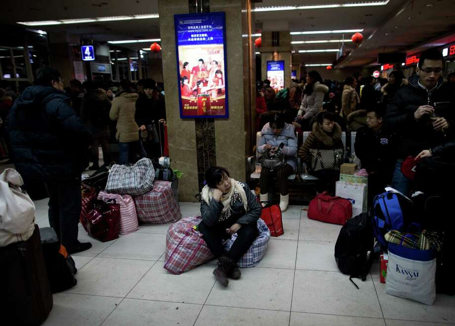 Passengers wait for their buses at a long-distance bus station in Shanghai Friday Feb. 8, 2013. Snow has hit several part of China on Friday, disrupting traffic as millions of Chinese are on their way for family reunion during the Spring Festival holidays, begining Feb. 10. Photo: Associated Press / CHINATOPIX