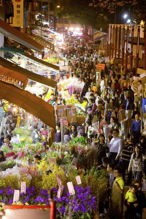 Shoppers browse flowers displayed for sale for the Lunar New Year on Flower Market Road in the shopping district of Mongkok in Hong Kong, China, on Thursday, Feb. 7, 2013. Hong Kong's stock market will be shut for three days next week for the Lunar New Year holidays, while markets in mainland China will be closed for the whole week. Photo: Lam Yik Fei, Bloomberg / © 2013 Bloomberg Finance LP