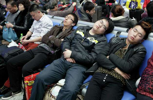 Passengers nap as they wait to board trains at Hongqiao Railway Station in Shanghai, China, on Sunday, Feb. 3, 2013. Forecasts of snow and rain across China threaten to disrupt the travel plans of millions of Chinese heading home for the Lunar New Year holidays that start Feb. 9, the national weather agency warned. Photo: Tomohiro Ohsumi, Bloomberg / © 2013 Bloomberg Finance LP