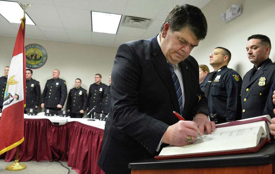 New Troy Police Commissioner Anthony Magnetto signs the oath of office during his swearing in ceremony at Troy City Hall Friday Feb. 8, 2013.   (John Carl D'Annibale / Times Union) Photo: John Carl D'Annibale / 00021032A