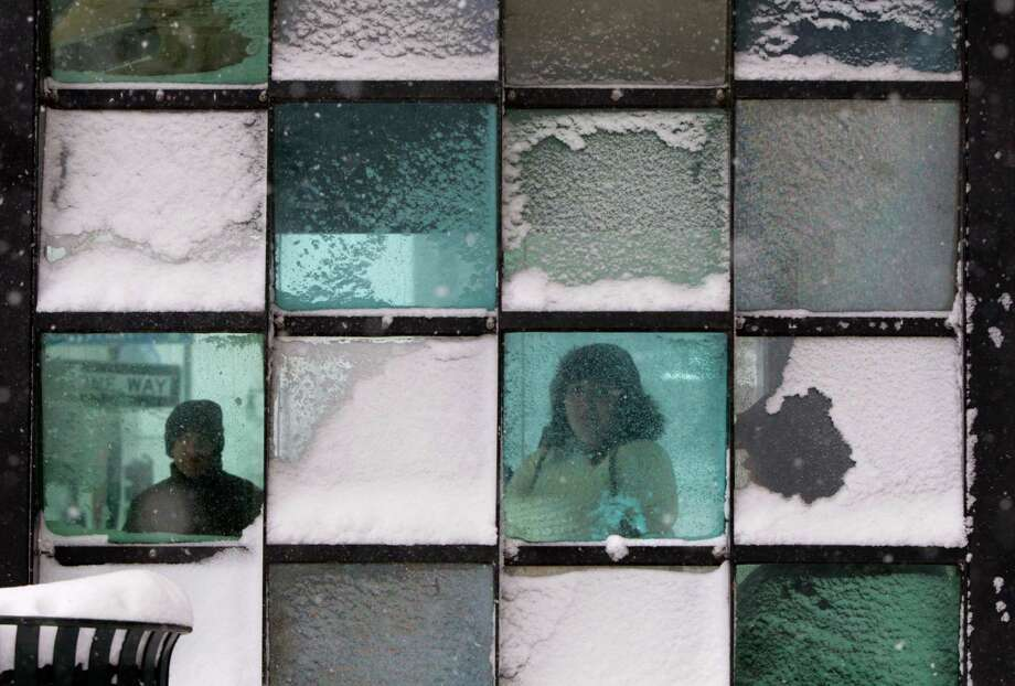 Riders wait in a bus stop where color-tinted windows collect snow during a storm, Friday, Feb. 8, 2013, in Portland, Maine. The National Weather Service says a blizzard warning is issued Friday evening for the southern coast. The forecast calls for up to 2 feet of snow and winds gusting to 50 mph. Photo: Robert F. Bukaty, Associated Press / AP