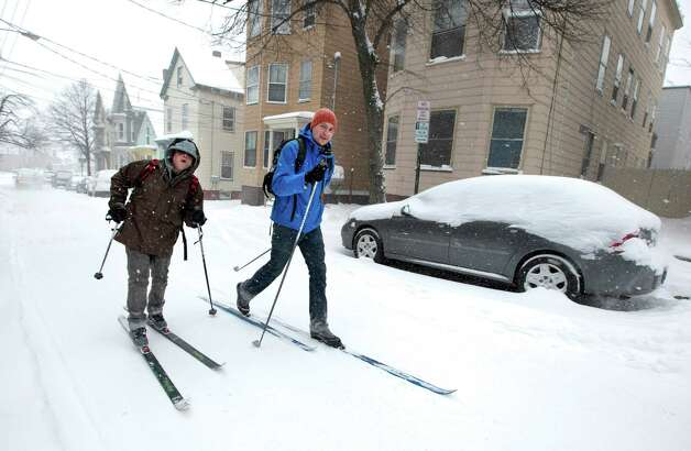Andre Tranchemantague, left, and Will Guerette, ski on a snow-covered road as they make there way to a bar during the early stages of a snow storm, Friday, Feb. 8, 2013, in Portland, Maine.  A snowstorm sweeping into Maine already has dumped half-a-foot of snow around Portland and contributed to a 19-car pileup. And it's just getting started. Chris Legrow from the National Weather Service says a blizzard warning is issued Friday evening for the southern coast, when the main storm arrives. The forecast calls for up to 2 feet of snow and winds gusting to 50 mph. Photo: Robert F. Bukaty, Associated Press / AP