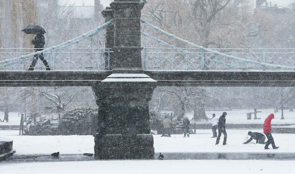 A man walks across a bridge in the snow in Boston Common on February 8, 2013 in Boston, Massachusett