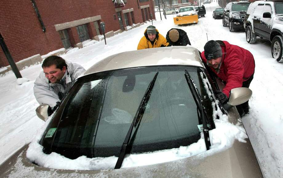 A group of men help push a sports car up a snow-covered street in the Old Port section of Portland, Maine, during a snow storm, Friday, Feb. 8, 2013. The storm is expected to dump up to two feet of snow on the region. Photo: Robert F. Bukaty, Associated Press / AP