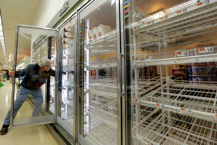 Jack Percoco of Cambridge, Mass. reaches into depleted shelves for milk at a supermarket in Somerville, Mass., Friday, Feb. 8, 2013. A major winter storm is heading toward the U.S. Northeast with up to 2 feet of snow expected for a Boston-area region that has seen mostly bare ground this winter. Photo: Elise Amendola, Associated Press / AP