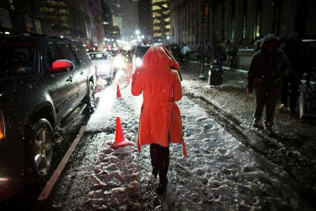 Snow falls on a pedestrian as she leaves the Rag & Bone Fall 2013 fashion collection show during Fashion Week, Friday, Feb. 8, 2013, in New York. Snow began falling across the Northeast on Friday, ushering in what was predicted to be a huge, possibly historic blizzard and sending residents scurrying to stock up on food and gas up their cars. Photo: John Minchillo, Associated Press / FR170537 AP