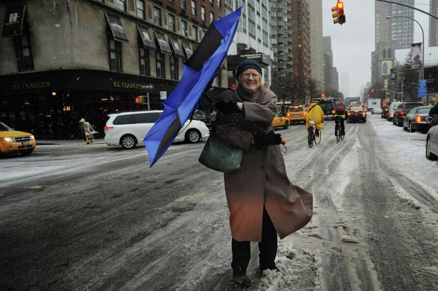 A woman struggles with her umbrella in New York on February 8, 2013 during a storm affecting the nor