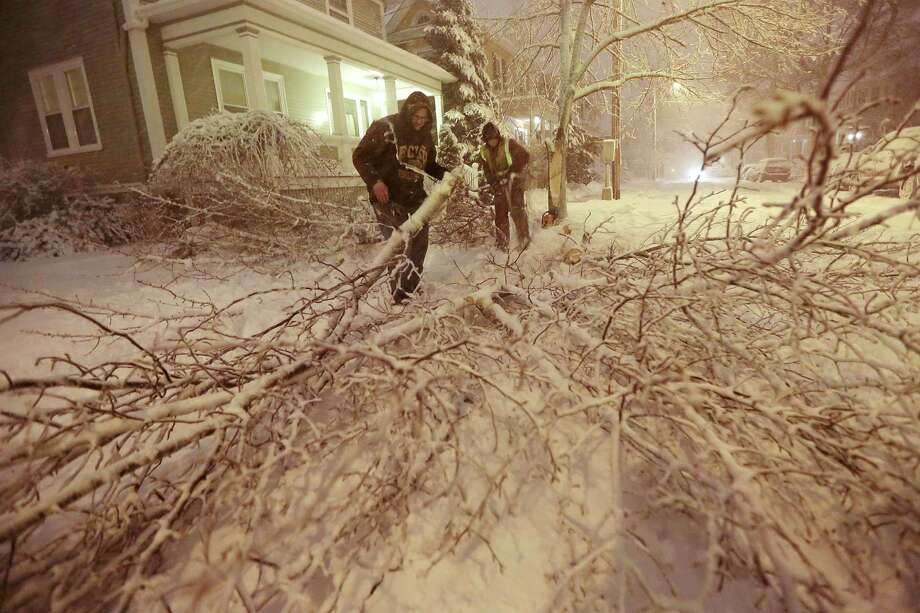 Mike Williams, left, and Louie Rodriguez of the New Bedford Forestry Department clear out a fallen tree from an intersection in New Bedford, Mass., on Friday, Feb. 8, 2013, after heavy snow and winds from a storm. Photo: Peter Pereira, Associated Press / Standard Times