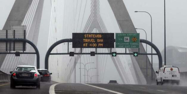 "Cars drive across the nearly empty Zakim Bridge in Boston prior to a mandatory statewide driving ban, Friday, Feb. 8, 2013. Mass. Gov. Deval Patrick declared a state of emergency Friday and banned travel on roads as of 4 p.m. as a blizzard that could bring nearly 3 feet of snow to the region began to intensify. As the storm gains strength, it will bring ""extremely dangerous conditions"" with bands of snow dropping up to 2 to 3 inches per hour at the height of the blizzard, Patrick said. Photo: Charles Krupa, Associated Press / AP"
